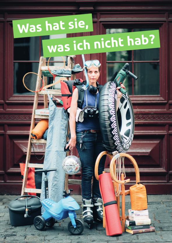 """Frau mit vielen Gegenständen bepackt, darüber der Spruch: """"Was hat sie, was ich nicht hab?"""""""