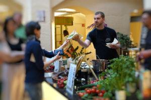 Eine Besucherin des Marktes kauft eine Kostprobe bei einem Showkoch ein.