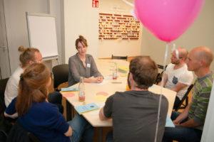 Eine Referentin diskutiert mit den Teilnehmern des Workshops an einem großen Tisch.
