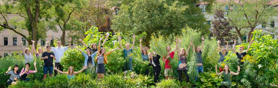 Auf dem Foto stehen alle Mitarbeiter des Verein in einem grünen Beet.